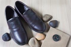 Καφετιά παπούτσια δέρματος ατόμων με το βιβλίο σημειώσεων ή ημερολόγιο με την πυξίδα Στοκ εικόνα με δικαίωμα ελεύθερης χρήσης