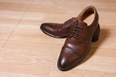 Καφετιά παπούτσια ατόμων δέρματος στο ξύλινο έδαφος Στοκ Εικόνα