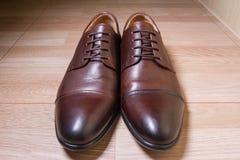 Καφετιά παπούτσια ατόμων δέρματος στο ξύλινο έδαφος Στοκ φωτογραφίες με δικαίωμα ελεύθερης χρήσης