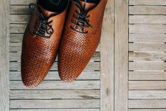 Καφετιά παπούτσια ατόμων με τις δαντέλλες στο ξύλινο υπόβαθρο Στοκ Φωτογραφία