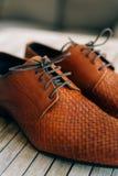 Καφετιά παπούτσια ατόμων με τις δαντέλλες στο ξύλινο υπόβαθρο Στοκ εικόνες με δικαίωμα ελεύθερης χρήσης