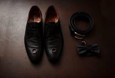 Καφετιά παπούτσια ατόμων ` s δέρματος με τα εξαρτήματα και τα γαμήλια δαχτυλίδια SE Στοκ Εικόνες