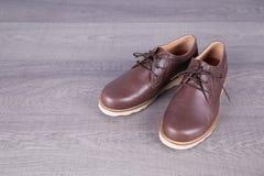 Καφετιά παπούτσια ατόμων ` s δέρματος στο ξύλινο υπόβαθρο Στοκ εικόνες με δικαίωμα ελεύθερης χρήσης