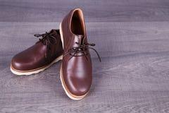 Καφετιά παπούτσια ατόμων ` s δέρματος στο ξύλινο υπόβαθρο Στοκ εικόνα με δικαίωμα ελεύθερης χρήσης