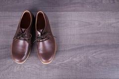 Καφετιά παπούτσια ατόμων ` s δέρματος στο ξύλινο υπόβαθρο Στοκ φωτογραφίες με δικαίωμα ελεύθερης χρήσης