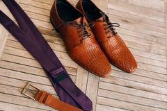 Καφετιά παπούτσια ατόμων ` s με τις δαντέλλες σε ένα ξύλινο υπόβαθρο και ένα καφέ Στοκ εικόνες με δικαίωμα ελεύθερης χρήσης