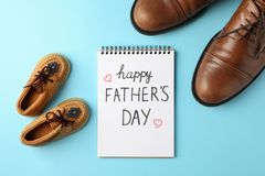 Καφετιά παπούτσια δέρματος, παπούτσια των παιδιών και σημειωματάριο με την ευτυχή ημέρα πατέρων επιγραφής στο υπόβαθρο χρώματος στοκ φωτογραφίες με δικαίωμα ελεύθερης χρήσης