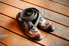 Καφετιά παπούτσια ζωνών και δέρματος στο ξύλινο πάτωμα Εξαρτήματα ατόμων Στοκ Φωτογραφία