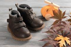Καφετιά παπούτσια παιδιών δέρματος στο ξύλινο σκηνικό η έννοια φθινοπώρου απομόνωσε το λευκό Στοκ φωτογραφία με δικαίωμα ελεύθερης χρήσης