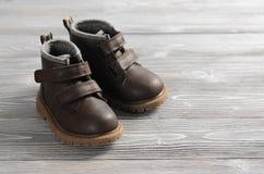 Καφετιά παπούτσια παιδιών δέρματος στο ξύλινο σκηνικό Στοκ Φωτογραφία