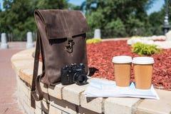 Καφετιά τσάντα δέρματος με τη κάμερα, το χάρτη και τα μίας χρήσης φλυτζάνια καφέ στο πάρκο Στοκ Φωτογραφία