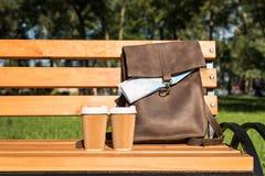 Καφετιά τσάντα δέρματος με το χάρτη και μίας χρήσης φλυτζάνια καφέ στον ξύλινο πάγκο Στοκ Εικόνες