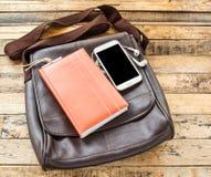 Καφετιά τσάντα δέρματος, σημειωματάριο, έξυπνα τηλέφωνο και ακουστικό στο ξύλινο TA στοκ εικόνες με δικαίωμα ελεύθερης χρήσης