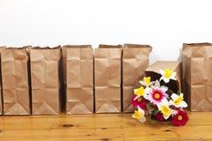 Καφετιά τσάντες και λουλούδια Στοκ Φωτογραφία