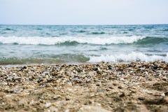 Καφετιές μικρές πέτρες χαλικιών στο πρώτο πλάνο με τη θολωμένη θάλασσα Στοκ Φωτογραφία
