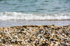 Καφετιές μικρές πέτρες χαλικιών στο πρώτο πλάνο με τη θολωμένη θάλασσα Στοκ Εικόνες