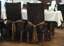 Καφετιές ντυμένες καρέκλες με τα τόξα στο εστιατόριο Στοκ φωτογραφία με δικαίωμα ελεύθερης χρήσης