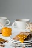 Καφετιές σουηδικές κροτίδες ψωμιού σίκαλης τραγανές με την πορτοκαλιά μαρμελάδα και τα φλυτζάνια του τσαγιού Στοκ φωτογραφία με δικαίωμα ελεύθερης χρήσης