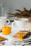 Καφετιές σουηδικές κροτίδες ψωμιού σίκαλης τραγανές με την πορτοκαλιά μαρμελάδα και τα φλυτζάνια του τσαγιού Στοκ Εικόνες
