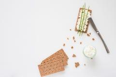 Καφετιές σουηδικές κροτίδες ψωμιού σίκαλης τριζάτες με το τυρί εξοχικών σπιτιών, που διακοσμείται με το λεπτό πράσινο κρεμμύδι Στοκ Εικόνες