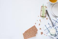 Καφετιές σουηδικές κροτίδες ψωμιού σίκαλης τριζάτες με το τυρί εξοχικών σπιτιών με τα πιάτα και το φλυτζάνι τσαγιού Στοκ φωτογραφίες με δικαίωμα ελεύθερης χρήσης