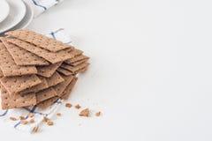 Καφετιές σουηδικές κροτίδες ψωμιού σίκαλης τριζάτες στο κομμάτι του υφάσματος με τα πιάτα στο άσπρο υπόβαθρο με το διάστημα για τ Στοκ φωτογραφίες με δικαίωμα ελεύθερης χρήσης