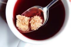 Καφετιοί κύβοι ζάχαρης στο τσάι φρούτων στοκ εικόνες