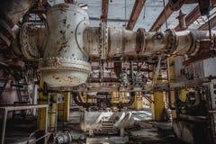 Καύσιμα μετάλλων και σκουριασμένος εξοπλισμός ηλεκτρικής παραγωγής στο εγκαταλειμμένο εσωτερικό εργοστασίων Στοκ Εικόνες