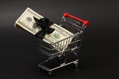 Καλάθι αγορών με το σωρό των αμερικανικών λογαριασμών εκατό δολαρίων χρημάτων με το μαύρο τόξο μέσα στη στάση στο μαύρο υπόβαθρο Στοκ φωτογραφίες με δικαίωμα ελεύθερης χρήσης