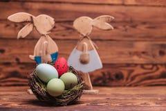 Καλάθι αυγών Πάσχας μπροστά από τα ξύλινα κουνέλια Στοκ φωτογραφία με δικαίωμα ελεύθερης χρήσης
