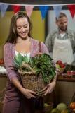 Καλάθι εκμετάλλευσης γυναικών των πράσινων φυλλωδών λαχανικών στο μανάβικο Στοκ Φωτογραφία