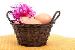 Καλάθι καλάμων με τα αυγά Πάσχας και τη ρόδινη κορδέλλα διακοσμήσεων Στοκ Εικόνες