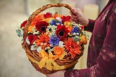 Καλάθι με μια ανθοδέσμη των ζωηρόχρωμων λουλουδιών Στοκ Φωτογραφίες