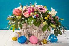 Καλάθι με τα διακοσμητικά λουλούδια και τα ζωηρόχρωμα αυγά Πάσχας Στοκ φωτογραφία με δικαίωμα ελεύθερης χρήσης