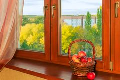 Καλάθι με τα μήλα στο ξύλινο παράθυρο το φθινόπωρο στοκ εικόνα με δικαίωμα ελεύθερης χρήσης