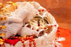 καλάθι με τα παιχνίδια Χριστουγέννων και τα χέρια ρολογιών Στοκ Φωτογραφίες