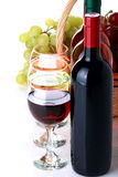 Καλάθι με τα σταφύλια και τα μπουκάλια κρασιού Στοκ Εικόνες