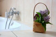 Καλάθι με την πετσέτα και λουλούδια στο λουτρό Στοκ εικόνες με δικαίωμα ελεύθερης χρήσης