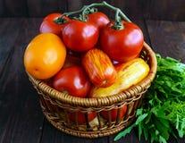 Καλάθι με τις ντομάτες των διαφορετικών ποικιλιών και sheaf arugula στο σκοτεινό ξύλινο υπόβαθρο Στοκ εικόνα με δικαίωμα ελεύθερης χρήσης
