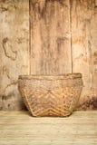 Καλάθι μπαμπού στην ύφανση χαλιών και το ξύλινο υπόβαθρο πινάκων Στοκ Εικόνα