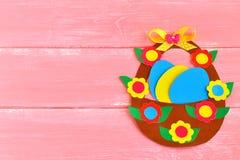 Καλάθι Πάσχας με τα αυγά και τα λουλούδια φιαγμένα από χαρτόνι, στο ρόδινο ξύλινο υπόβαθρο, με το διάστημα για τα συγχαρητήρια σε Στοκ Εικόνες