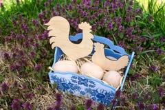 Καλάθι Πάσχας με τα ξύλινους αυγά, τον κόκκορα και το κοτόπουλο Στοκ Φωτογραφία