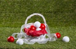 Καλάθι Πάσχας με τις σφαίρες και τις κορδέλλες γκολφ Στοκ εικόνες με δικαίωμα ελεύθερης χρήσης