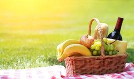 Καλάθι πικ-νίκ με τα τρόφιμα στη χλόη Στοκ Φωτογραφία