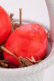 Καλάθι των λαμπρά χρωματισμένων αυγών Πάσχας Στοκ Εικόνες