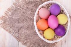 Καλάθι των χρωματισμένων αυγών στον ξύλινο πίνακα Στοκ εικόνες με δικαίωμα ελεύθερης χρήσης