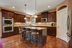 Καλά αναδιαμορφωμένο εσωτερικό δωματίων κουζινών με τα σκοτεινά ξύλινα γραφεία στοκ εικόνες