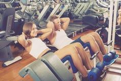 Καλά - εκπαιδευμένοι νεαρός άνδρας και γυναίκα που εκπαιδεύουν τους κοιλιακούς μυς στο γ Στοκ Εικόνα
