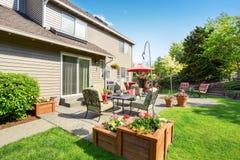 Καλά κρατημένος κήπος στο κατώφλι με τη συγκεκριμένη περιοχή patio πατωμάτων στοκ εικόνα με δικαίωμα ελεύθερης χρήσης