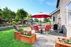 Καλά κρατημένος κήπος στο κατώφλι με τη συγκεκριμένη περιοχή patio πατωμάτων στοκ φωτογραφία